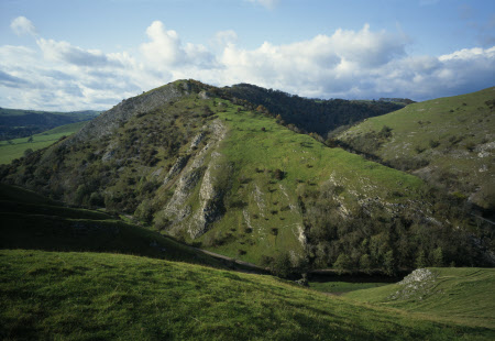 From the summit of Thorpe Cloud, Dovedale appears, protected by the limestone crags of Bunster Hill in the Peak District National Park, Derbyshire